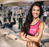 stock photo of stomach  - Portrait of smiling sporty woman in gym - JPG
