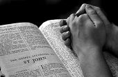 stock photo of prayer  - Hands of a person raised together in prayer with bible - JPG