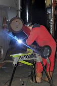 image of pipe-welding  - A welder welding a flange onto a pipe for a repair on a steam boiler in the background - JPG