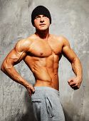 image of beanie hat  - Handsome man with muscular torso in beanie hat posing - JPG
