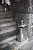 Old Metal Outdoor Lamps With Burning Candles Stands On Stone Stairs