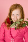Young Girl Is Holding A Red Rose Between Her Teeth