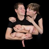 Young happy family posing with their ten days old newborn twin babies
