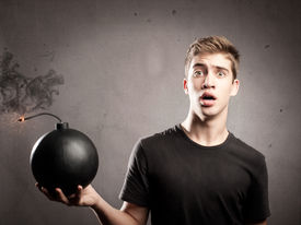 picture of anarchists  - scared young man holding an old fashioned bomb - JPG