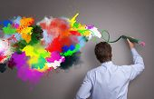 pic of paint spray  - Businessman painting abstract colorful design on gray background concept for  business creativity - JPG