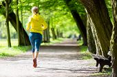 stock photo of dirt road  - Woman runner running and walking in park summer nature exercising in bright forest outdoors - JPG