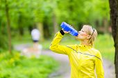 image of dirt road  - Beautiful woman runner drinking water from bottle during running and walking in park summer nature exercising in bright forest outdoors - JPG