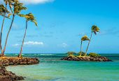 foto of off-shore  - A tiny rock island with palm trees off the coast of Kahala Beach on the south shore of Oahu Hawaii - JPG