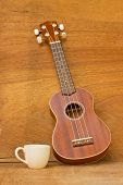 stock photo of ukulele  - Coffee and Ukulele on a wood background - JPG
