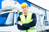 stock photo of lift truck  - builder or driver standing in front of pallet transporter or lift fork truck on construction or building site - JPG