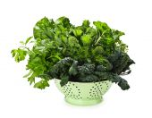 stock photo of roughage  - Dark green leafy fresh vegetables in metal colander isolated on white - JPG