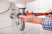 stock photo of sanitation  - Close-up Of Male Plumber Fitting Sink Pipe In Bathroom
