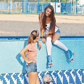 image of roller-skating  - two beautiful young girls in an empty pool one wearing roller skates the other  - JPG