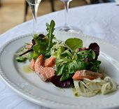 stock photo of rocket salad  - The salad with salmon is situated on the white plate - JPG