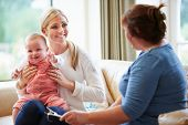 picture of young baby  - Health Visitor Talking To Mother With Young Baby - JPG