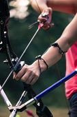 picture of longbow  - Selective focus on the bow which is pulled at something by lovely young fair - JPG