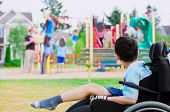 foto of disability  - Disabled little boy in wheelchair sadly watching children play on playground - JPG