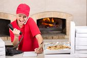 stock photo of take out pizza  - Delivery woman of pizza is taking orders by phone. Several boxes of pizza near her. ** Note: Shallow depth of field - JPG