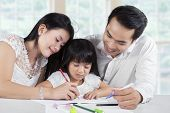 image of homework  - Portrait of two parents assist their daughter doing homework at home - JPG