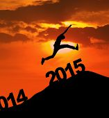 picture of escalator  - Man jumping over number of 2015 on the hill at sunset  - JPG