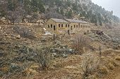 foto of snowy hill  - Large stone building on a hill in a Utah ghost town on a snowy winter day - JPG