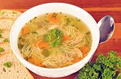 stock photo of chicken  - Bowl with chicken soup with vegetables and chicken meat toasted bread spoon on wooden table - JPG