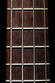 picture of fret  - Detail of the fret board of a bass guitar on a dark background - JPG