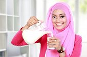 stock photo of muslimah  - portrait of beautiful young woman pouring milk into a glass - JPG