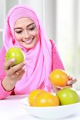 foto of muslimah  - portrait of young muslim woman pick over between apple and orange for breakfast - JPG