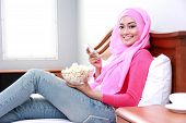 stock photo of muslimah  - portrait of young muslim woman holding mobilephone and a bowl of popcorn on bed - JPG