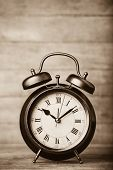 stock photo of analog clock  - Retro alarm clock on a table - JPG