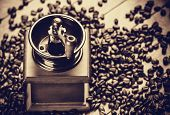 foto of threshing  - Coffee grinder with coffee grains on a wooden table - JPG