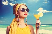 foto of redhead  - Pretty redhead women with cocktail on the beach - JPG