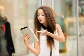 picture of shopping center  - Beautiful young girl paying by credit card for shopping with a laptop against the background of the shopping center - JPG