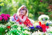 stock photo of baby easter  - Cute curly little girl in a red summer dress working in the garden watering first spring flowers on a sunny warm day - JPG