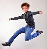 stock photo of sportive  - Portrait of a cute sportive cheerful happy boy with his hands up jumping and dancing - JPG