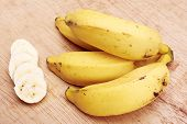 stock photo of bunch bananas  - Banana bunch and sliced bananas in wood background - JPG