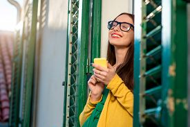 image of louvers  - Young woman in yellow sweater and glasses using mobile phone on the balcony with window shutters in old building - JPG