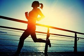 stock photo of japanese woman  - healthy lifestyle sports woman running on wooden boardwalk sunrise seaside - JPG