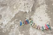picture of roping  - Grunge cement wall background texture with damaged pitted concrete and peeling plaster and rope with colorful plastic clothespin hanging on rope - JPG