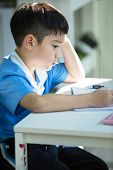 picture of homework  - Young asian boy doing his homework and thinking - JPG