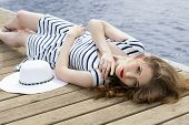stock photo of jetties  - pretty young woman with fashion striped dress hat and stylish make - JPG