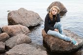 stock photo of snickers  - Beautiful blond Caucasian teenage girl sitting on coastal stones on the lake coast in Finland - JPG