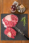 foto of veal  - Raw fresh cross cut veal shank and seasonings for making Osso Buco on wooden background - JPG