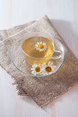 picture of chamomile  - cup of chamomile tea with chamomile flowers on flap of burlap - JPG