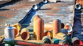 stock photo of spray can  - Used graffiti spray cans laying around at roof of abandoned warehouse - JPG