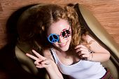stock photo of peace-sign  - Young girl Show Victory Sign smiling with curly hair wearing sunglasses with the American flag and a sign of peace - JPG