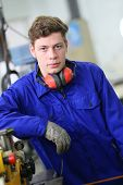 foto of plumber  - Portrait of plumber apprentice standing in workshop - JPG