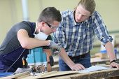 picture of carpentry  - Apprentice with adult in carpentry school working on wood - JPG