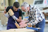 image of wood pieces  - Young apprentice with teacher working on piece of wood - JPG
